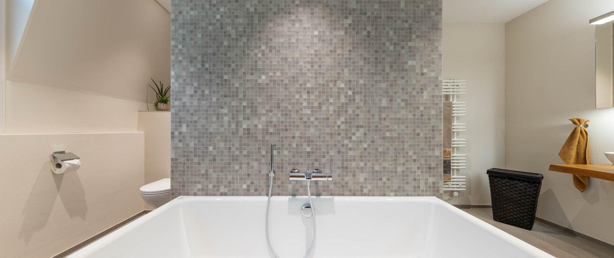 Badewanne vor stilvoller Mosaikwand